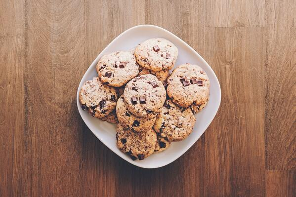 wooden table with square plate filled with chocolate chip cookies